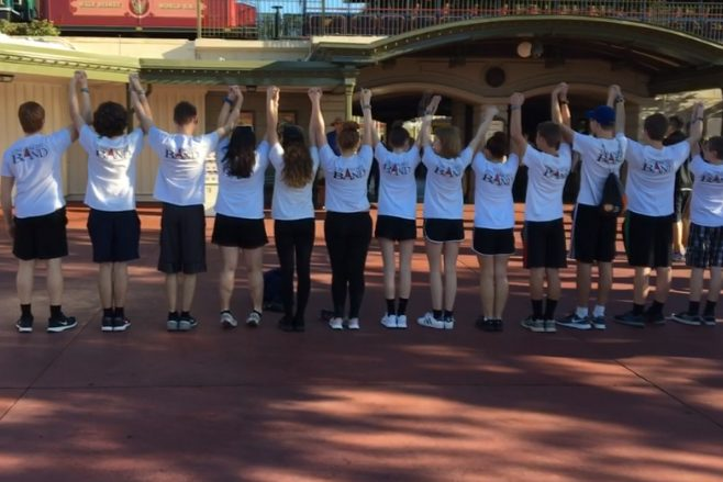 Lancer band members pose in their band shirts before entering the Magic Kingdom.