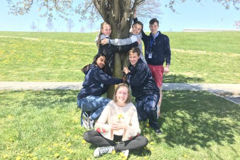 Journalism students show their love and enthusiasm for the environment by hugging a tree.