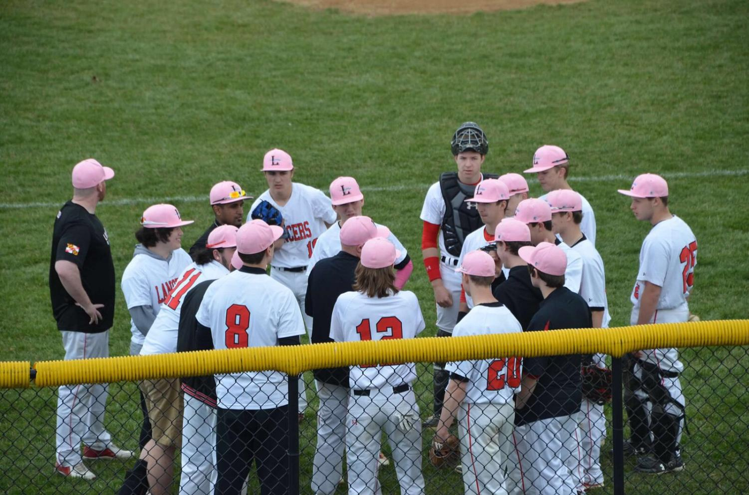 Lancer varsity baseball huddles up after a quick inning.