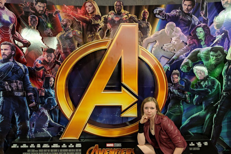 Elizabeth Anderson cosplays Scarlet Witch in front of Avengers: Infinity War poster