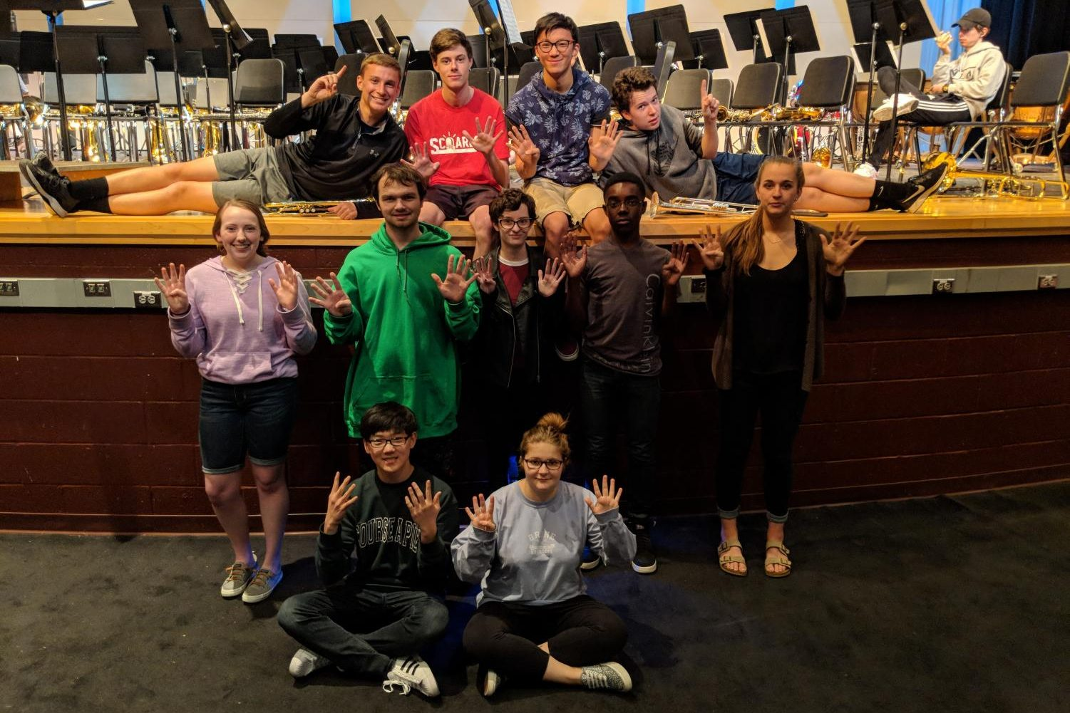 Andrew Nash, Matt Molineau, Richard Zhang, Evan Schalon, Mallory Safsten, Alex Pare, Erin Doyle, Charles Quansah, Olivia Weinel, Daniel Roberson, and Allie Hudson pose in front of the stage during symphonic band practice