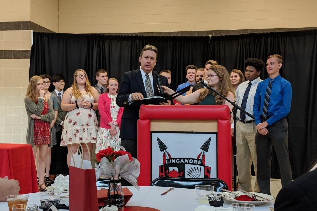 Allie Hudson and the senior class present their farewell gift to director Kevin Lloyd
