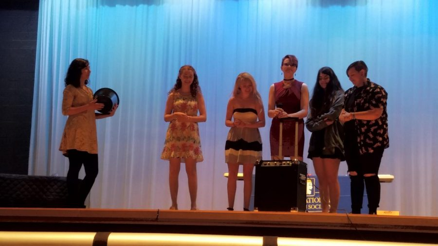 Rozmia Fattah, Katie Thomas, Cassidee Grunwald, Hannah Haught, and Shayden Jamison laugh while performing on stage together during final senior performances.