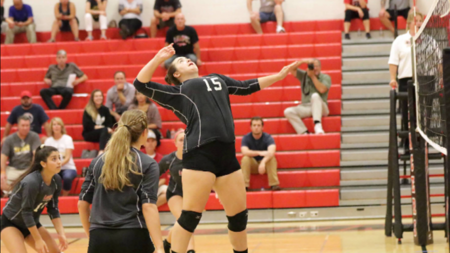 Junior Emma Frances goes up to return the ball the the other team.