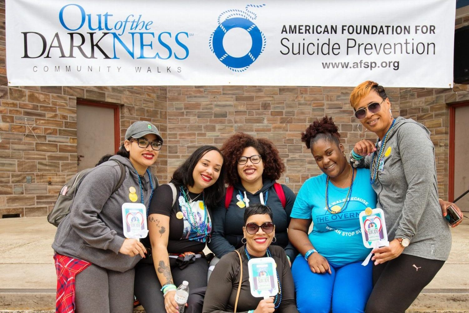 Out of the Darkness Walk 2017 participants pose in front of banner.