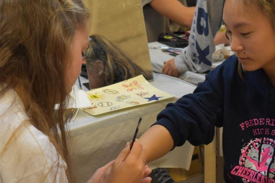 Junior Amanda Lindsay paints a ghost on junior Grace Gaydosh's arm.