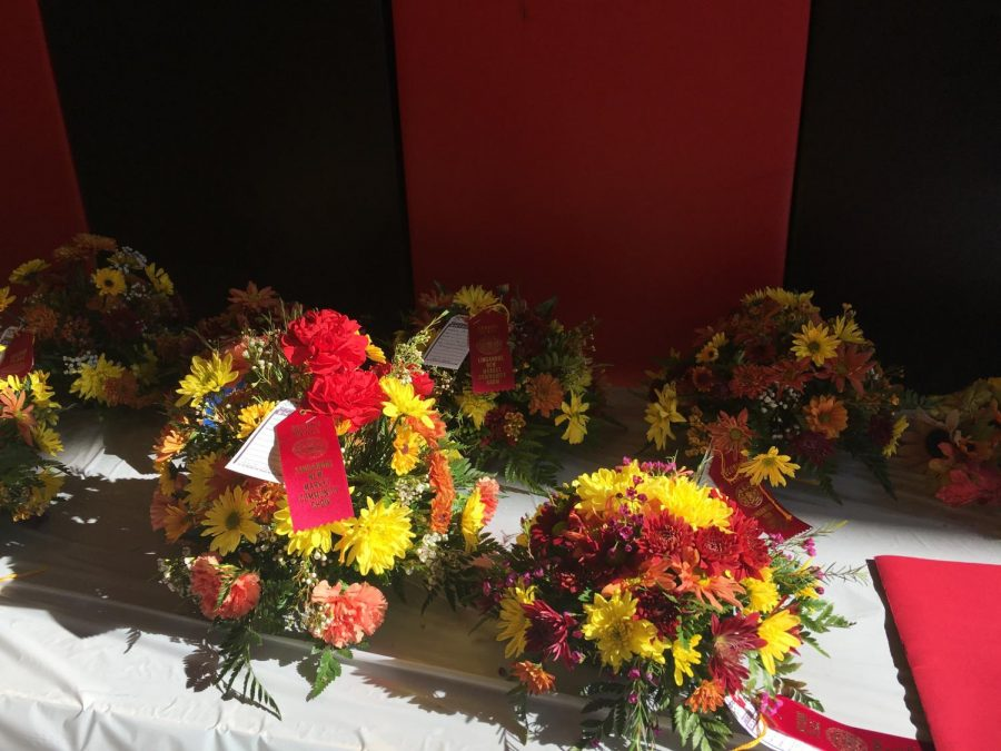 Flowers for auction are displayed on a table.