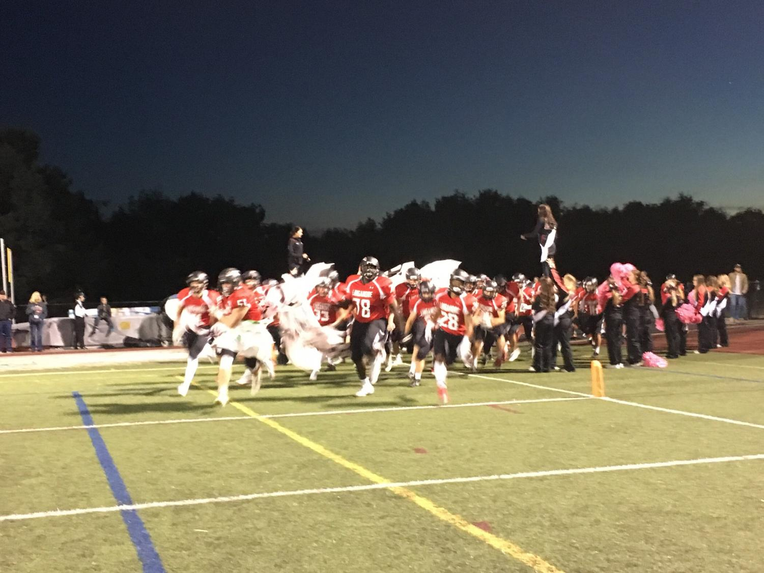 Tre Briscoe leads Linganore' football team out onto the field just before game time.