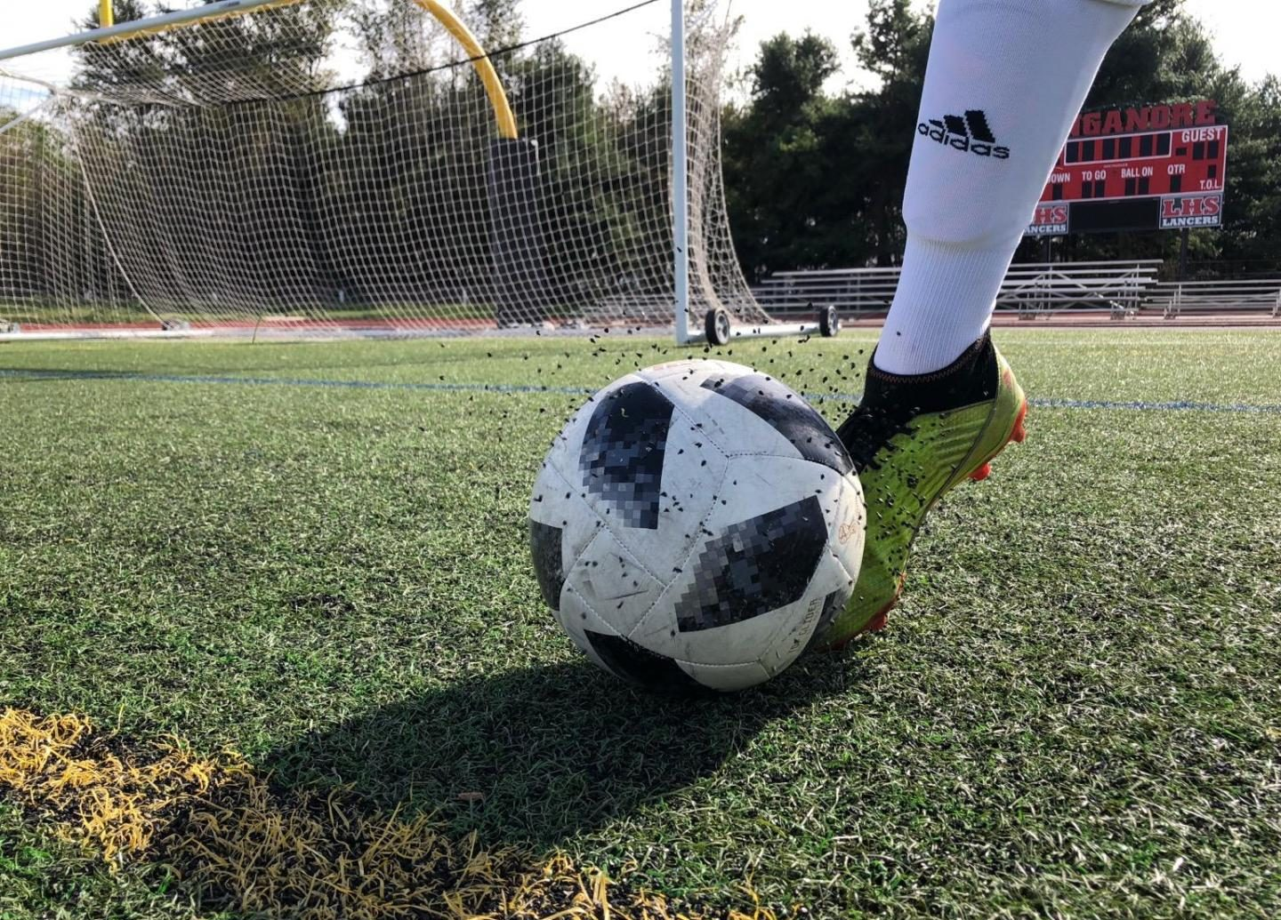 The tire crumb rubber rises high just from a bouncing soccer ball.