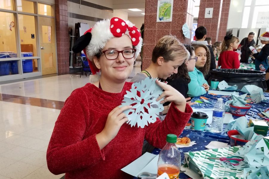 Sophomore+Charlotte+Moore+shows+off+a+paper+snowflake+at+a+crafts+table.