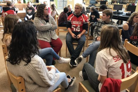 Students and staff converse in small groups over school and political issues.
