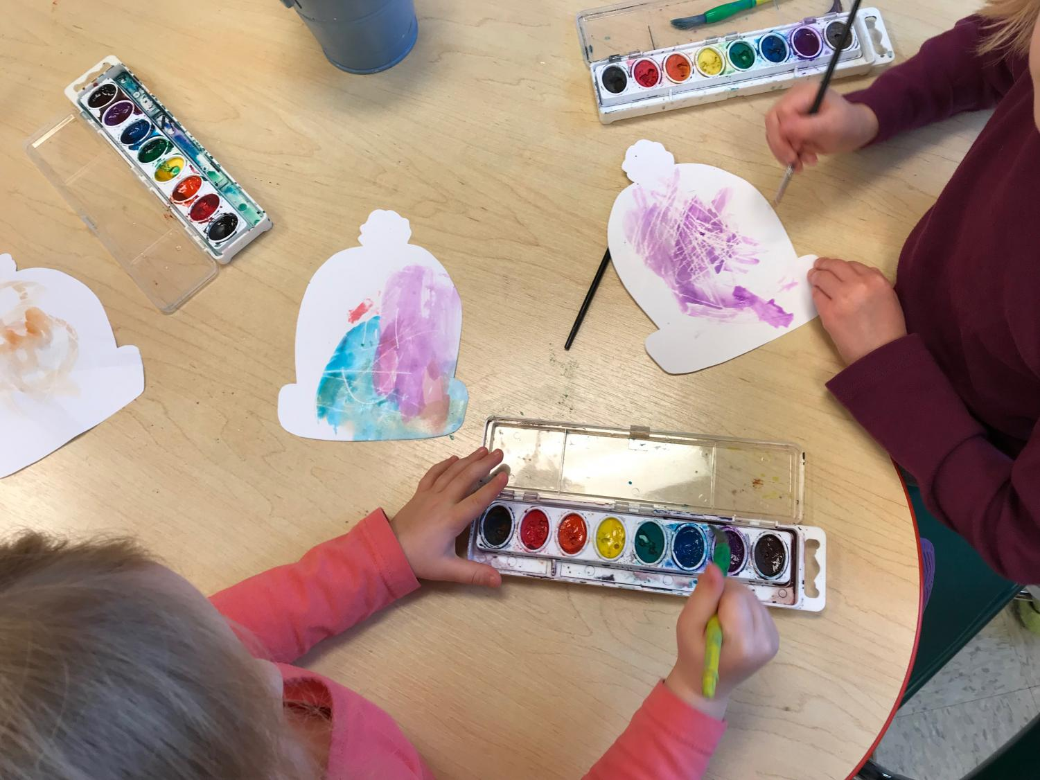 The Little Lancers are seen using watercolor to reveal their crayon art.