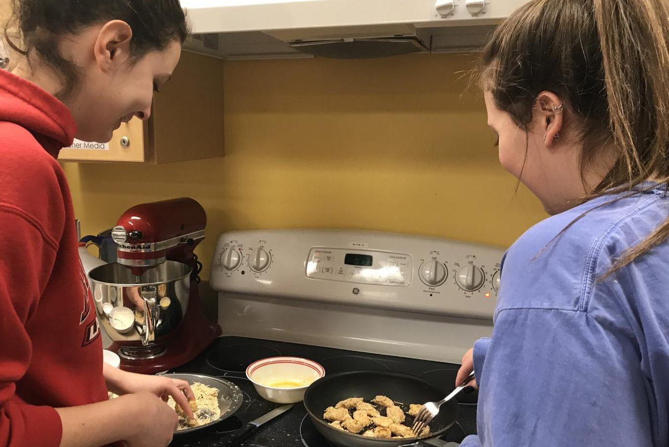 Seniors Devyn Watkins and Kristen Gagne cook chicken nuggets.
