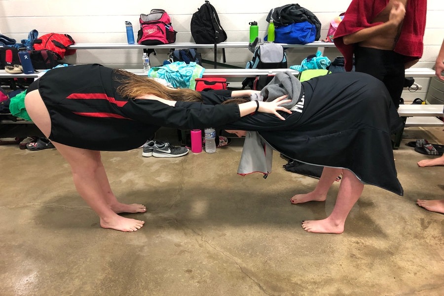 Freshman Emily Lotito and Lyra Garrett stretch their shoulders before their events.