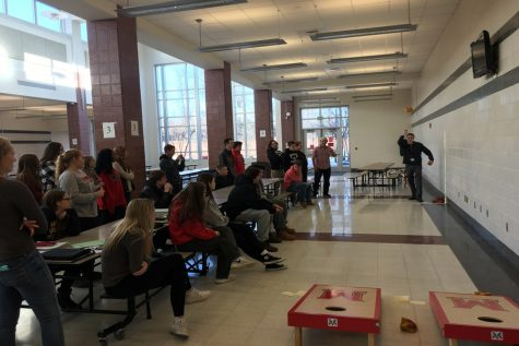 Students watch Mr. Halter demonstrate how to throw the bean bag.