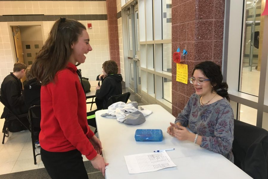 Sophomore Olivia Meyers buys a candy gram from junior NHS volunteer Alyson Zieg-Sniffen.