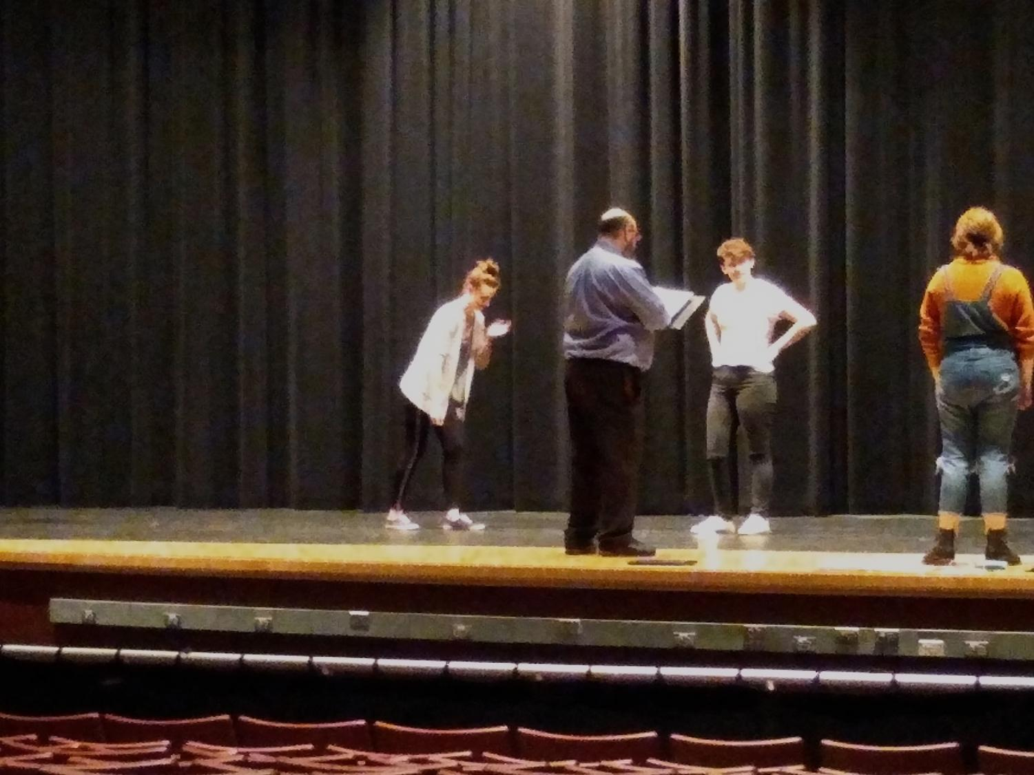 [left to right] Mr. Dan Lake assists Ashley Perise (Enchantress), Natalie Roth (Young Prince) and Beau Cameron (Student Director) with the prologue
