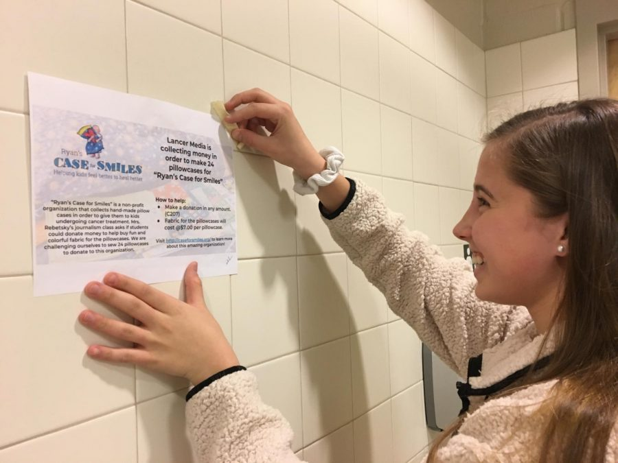 Bailey Bennett tapes flier promoting need for donations.