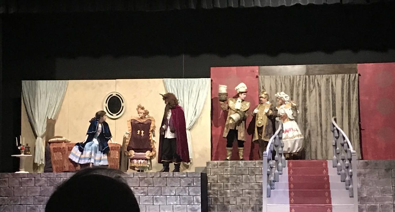 The Beast (David Kominars) tries to persuade Belle (Mackenzie Berry) to come to dinner. Madame de la Grande Bouche, Lumiere, Cogsworth and Mrs. Potts look on.