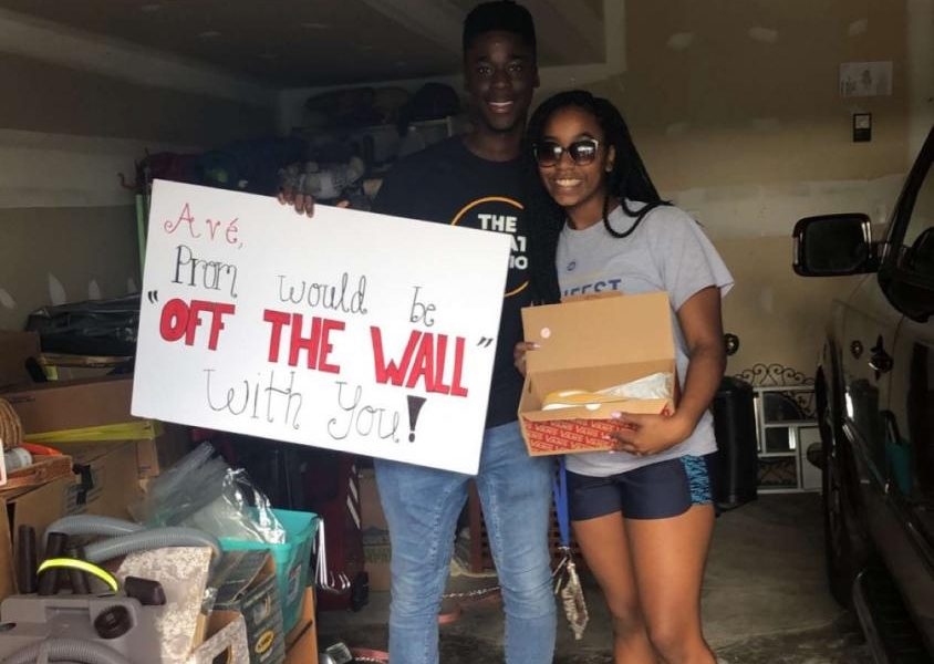 Kojo Benefo and Ave-Boghossian James posing for a cute picture with their unique promposal sign.