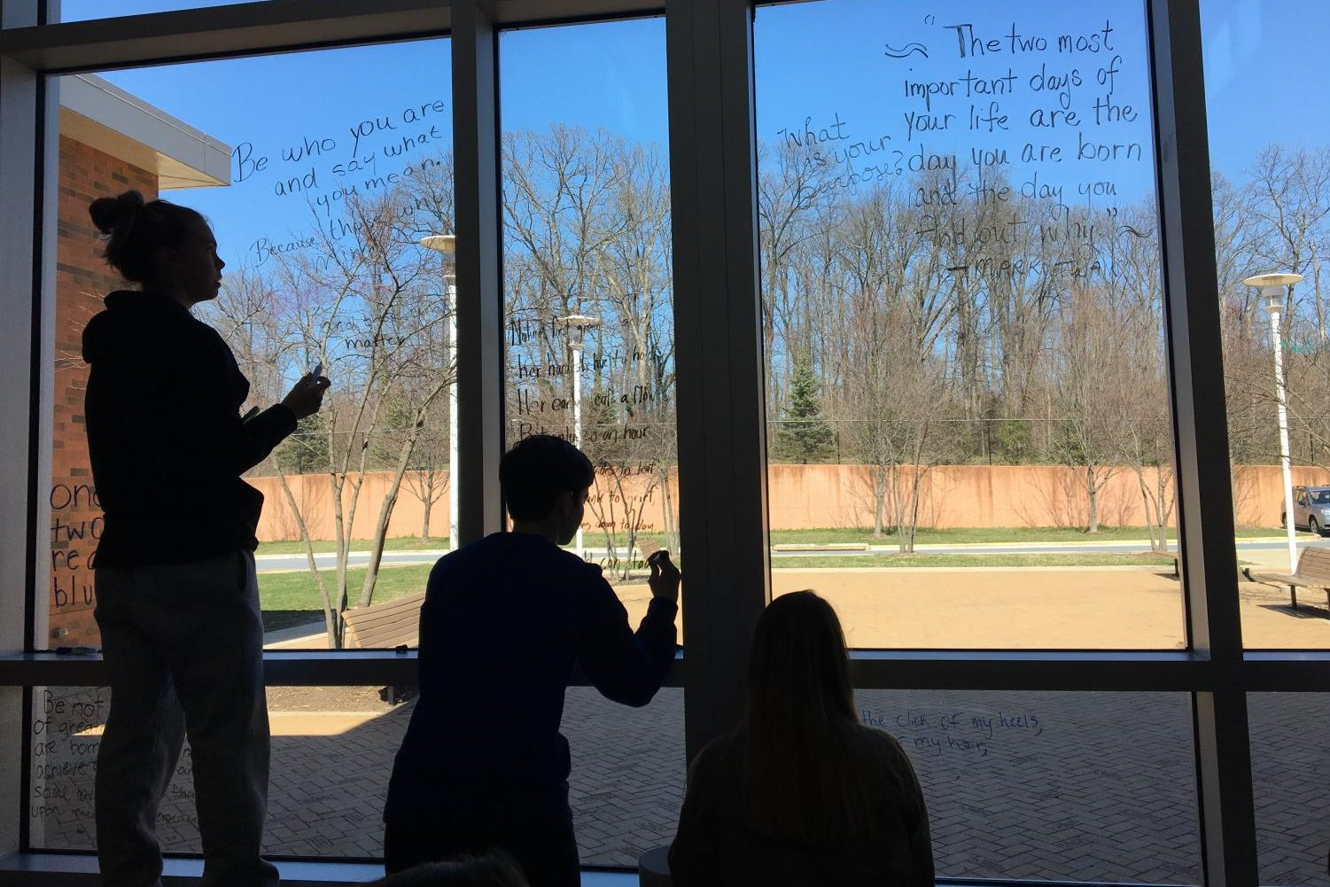 National English Honor Society members write poetry on the cafeteria windows.