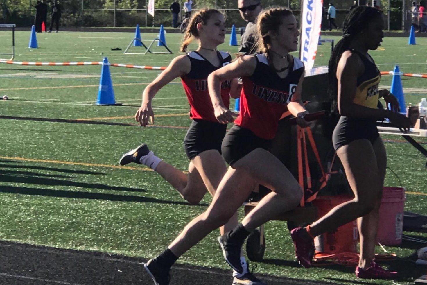 Freshman, Mikayla Moxley, passes the baton to freshman, Gemma Davies, in the 4x400 relay.