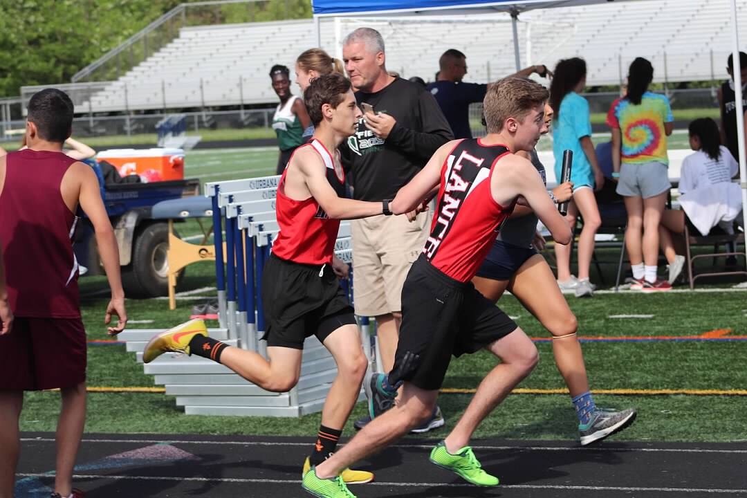 Zack Hunsaker hands the baton to Bailey Spore for the final leg of the 4x800 meter relay.