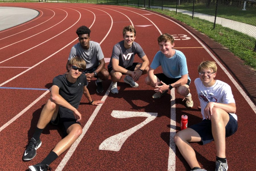 A few of the seniors on the boys track team pose in lane 7 for 7 days left of school.