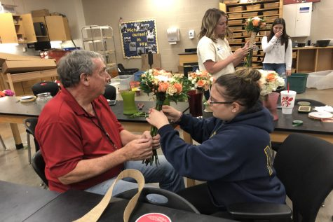 Mr. Hawthorne helps Lacee Larman arrange a bouquet for Saturday's wedding.