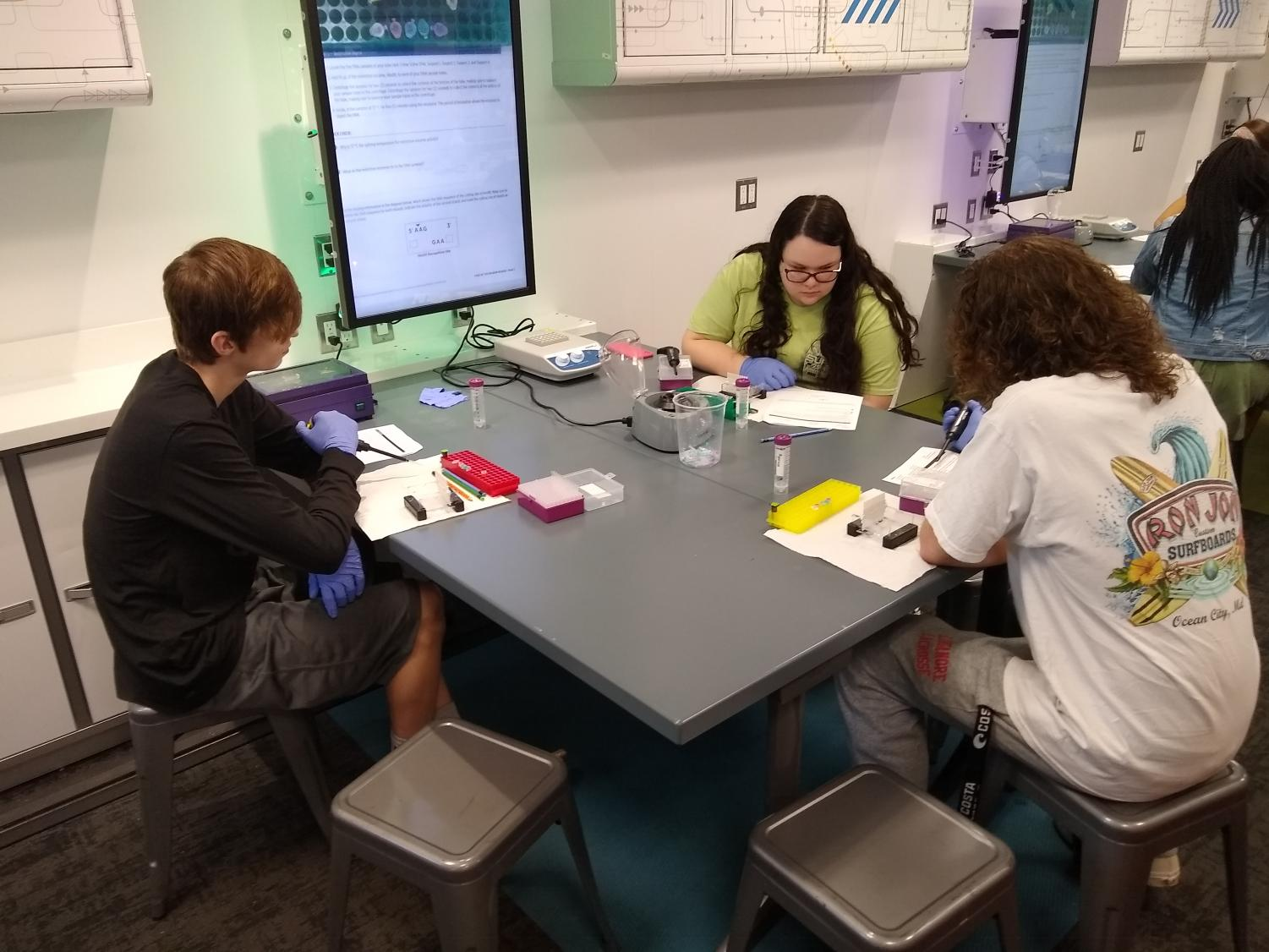 Zack Olliges, Elizabeth Gilmore and Joseph Hartung test DNA samples in the mobile lab.