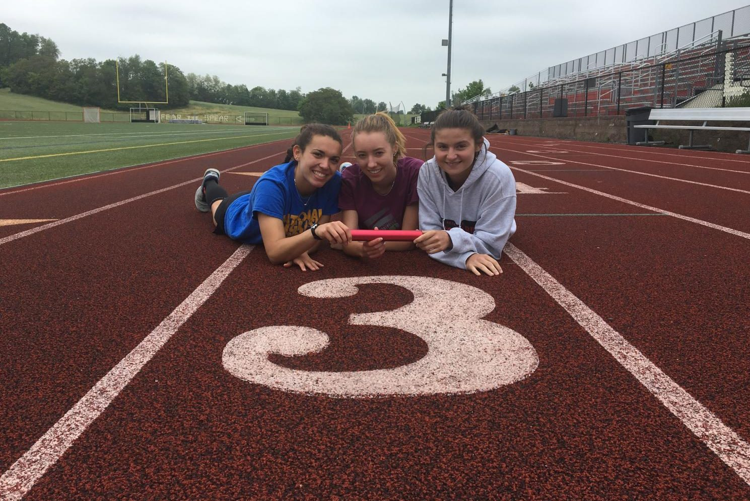 Seniors Morgan Matthews, Khelsa Connolly, and Savannah Sitler pose in front of lane three on the track with their relay baton.
