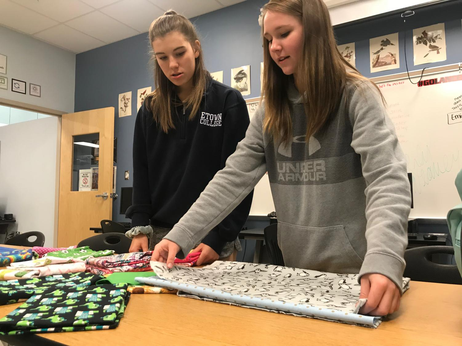 Elizabeth Rajnik and Sierra Rossman prepare the fabric for pillowcase assembly.