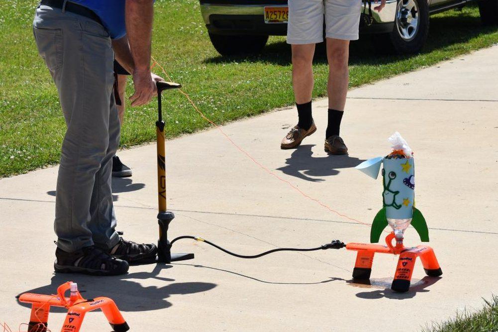 Mr. Eckard pumps a student's bottle rocket with air.