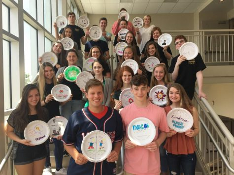 Journalism assembles for a group photo displaying their Paper Plates Award.