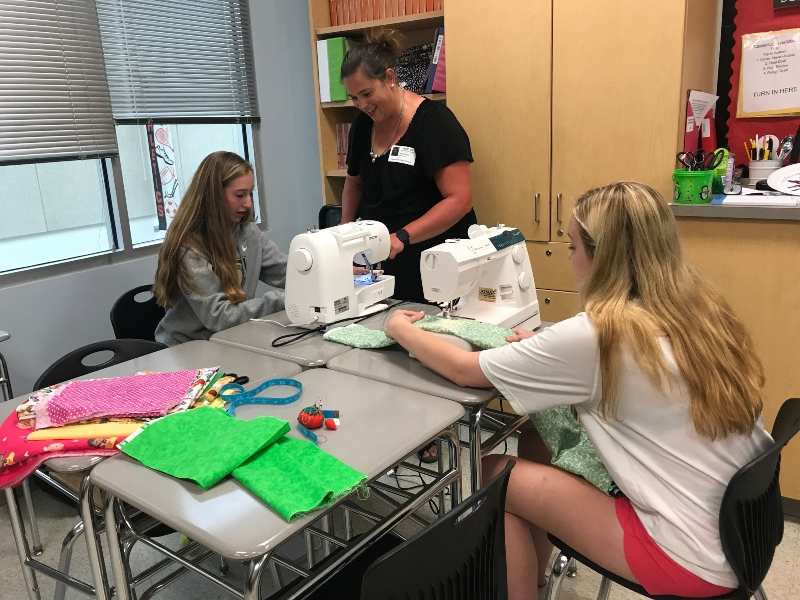 Howard County 4-H Program Adviser Chris Rein teaches Lancer Media members Madeline Williamson and Julie Walker how to sew a pillowcase.
