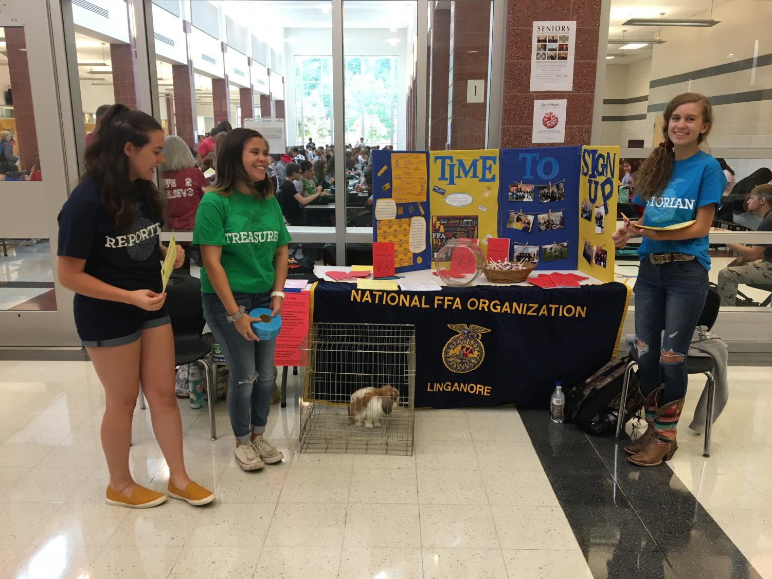 Peyron Johnson, Taylor Carbough, and Caroline Pellicier pose for a picture in front of their FFA stand.