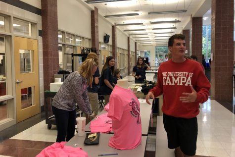 Taylor Ferguson sells a pink out shirt to Billy Higgins