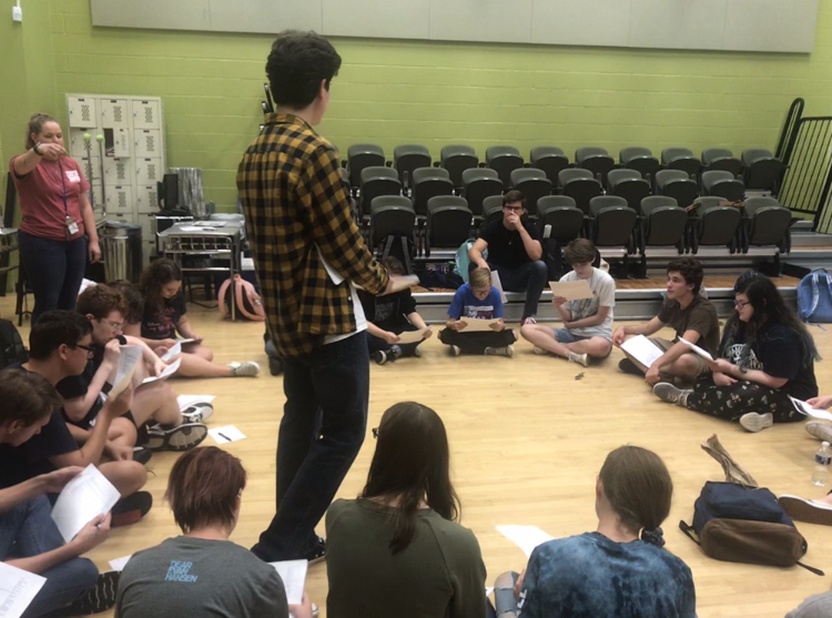 Student director, Jacob Blue, explains rehearsal breakdown to the cast.
