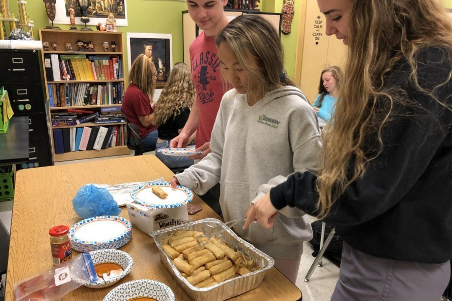 Grace Gaydosh serves club members Riley Sheehy and Leah Bolger egg rolls.