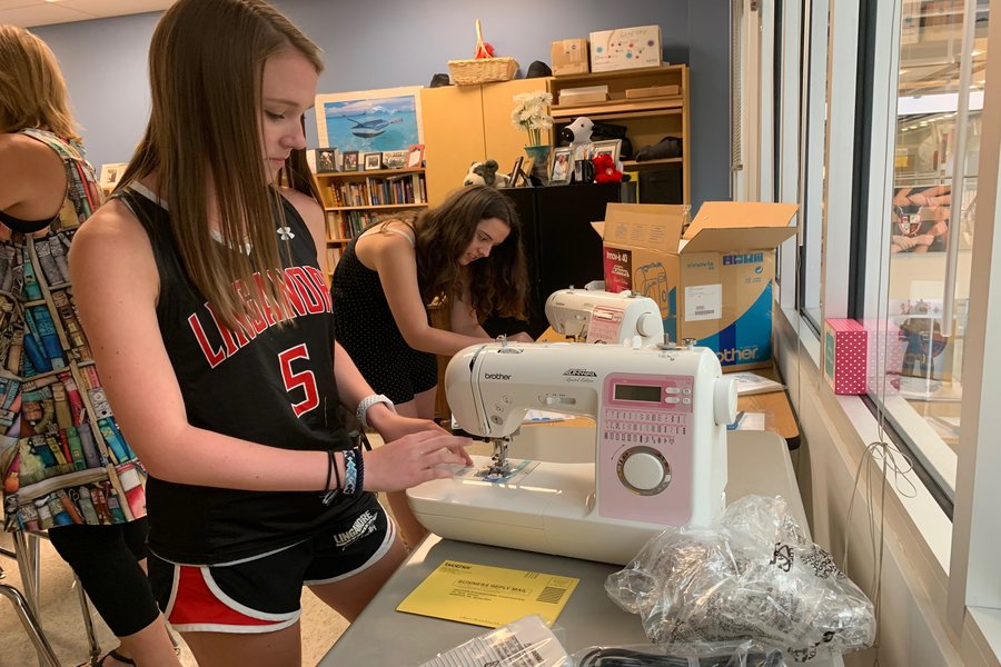 Sierra Rossman and Peyton Johnson prepare new sewing machines for the sew therapy PREP class.