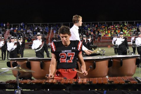 Football player Ethan Blache plays the marimba during the band's half-time performance.