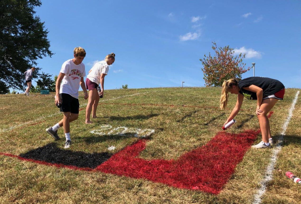 Kyle Bedard, Clare Beiter, and Taylor Ferguson work on the  Class of 2020 hill design.