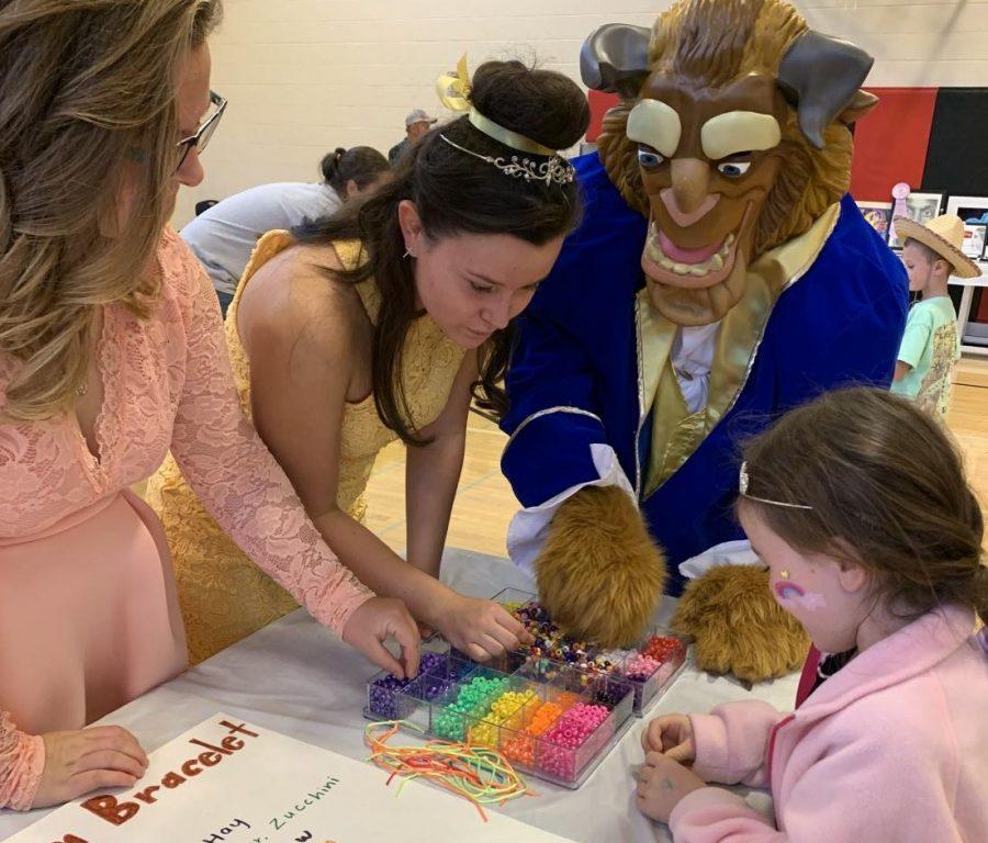 Ricky Cerveny, Beast, Tabitha Reeder, Belle, and Sarah Blankenship help Lucy Bolger  make a bracelet.