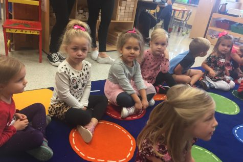 The Little Lancers sit on the carpet and wait for directions from the student teachers.