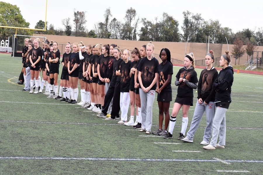 The varsity and JV field hockey teams made black melanoma inspired shirts using a reverse tie dye technique. This left an outline of a black ribbon. The team also used a bleach pen to write encouraging messages on the shirts.