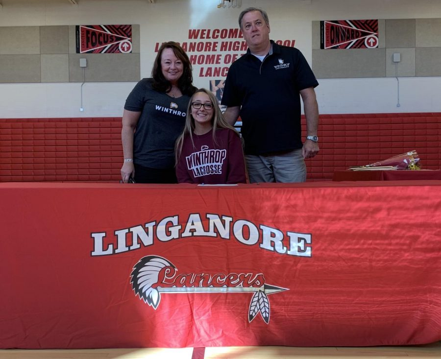 Cassie Nalepa poses for a photo with her parents after signing her National Letter of Intent.