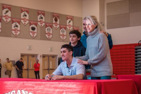 Lacrosse player, Roman LaRocco and his family pose for a picture after signing official documents.