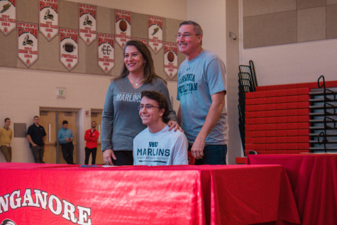 Aaron Oman poses with his parents after signing his National Letter of Intent.