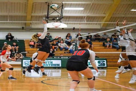 Lauren Ryan goes up above the net to tip the ball and win the point.