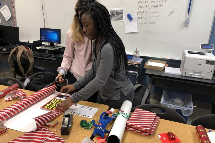 Juniors Maya Apau and Tabitha Moses wrap the books in festive wrapping paper.